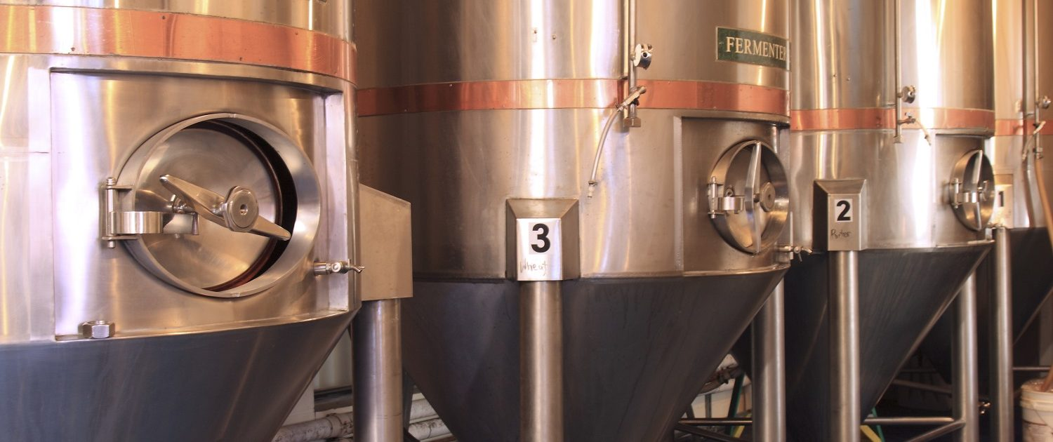 Cobalt blue epoxy floors enhance the beauty of the stainless steel and copper brewery equipment.