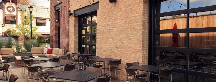 This image is Mickey Finn's outdoor patio, design elements include exposed steel frame and ten-foot garage style overhead doors that open to the dining room.