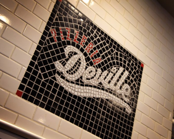 Pizzeria DeVille mosaic logo sign above the pizza oven.