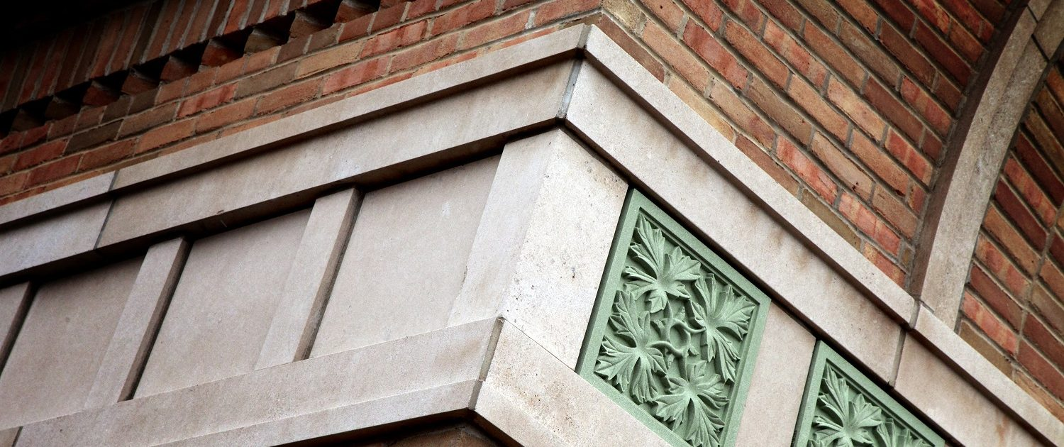 State Bank of The Lakes exterior oak leaf pattern green stone detail and brick & stone masonry.