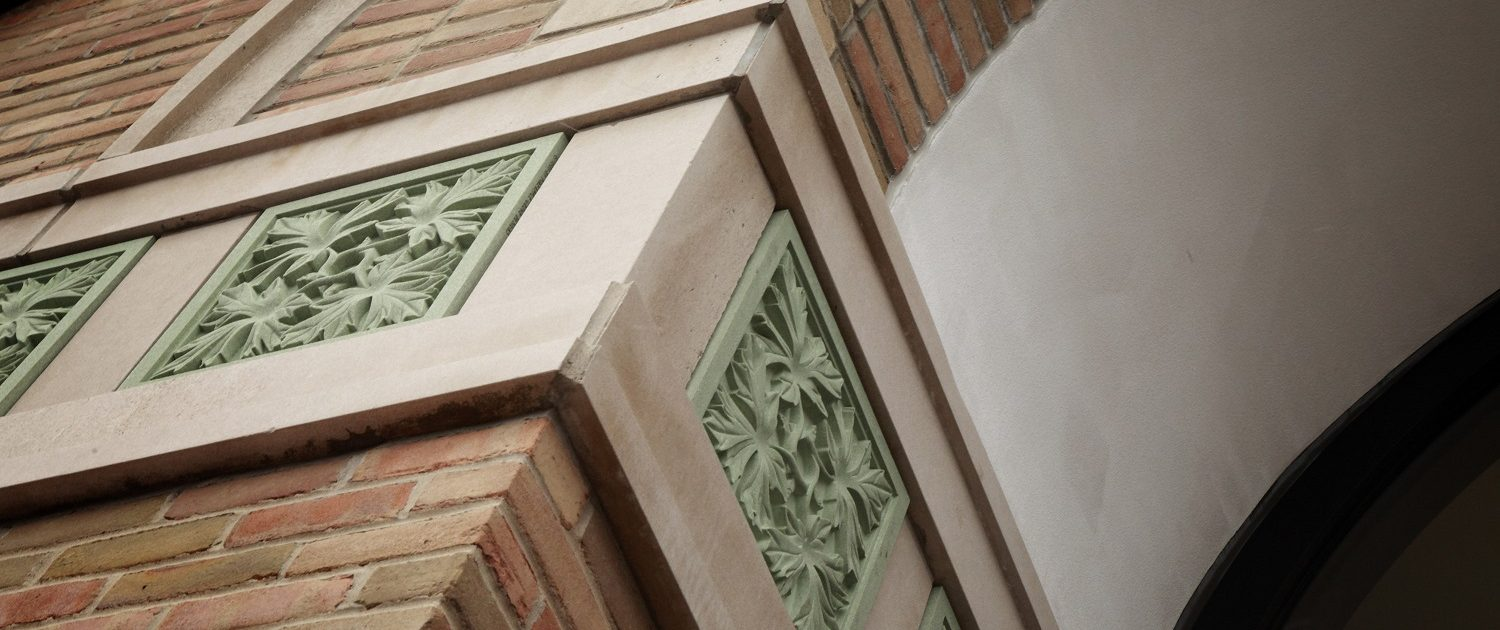 Exterior facade details of an oak leaf pattern in green stone suggesting growth, strength, and stability.